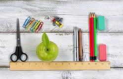 Schulbedarf in Übereinstimmung mit Machthaber auf dem weißen Desktop Lizenzfreie Stockfotos