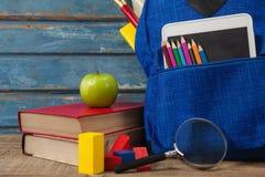 Schulbedarf, Apfel, digitale Tablette und Lupe auf Holztisch Lizenzfreies Stockfoto