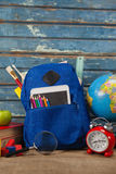Schulbedarf, Apfel, Kugel, digitale Tablette und Lupe auf Holztisch Stockfotografie