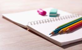 Schulbedarf auf Anmerkungsbuch stockfotografie