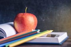 Schulbedarf auf dem Tisch Bücher, Bleistifte und Äpfel ist eine Sammlung des Studenten Konzept der Schule und der Bildung Lizenzfreie Stockfotografie