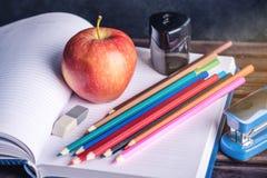 Schulbedarf auf dem Tisch Bücher, Bleistifte und Äpfel ist eine Sammlung des Studenten Konzept der Schule und der Bildung Stockfotografie