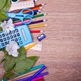 Schulbedarf auf einem hölzernen Hintergrund Lizenzfreie Stockfotografie
