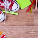 Schulbedarf auf einem hölzernen Hintergrund Lizenzfreie Stockbilder