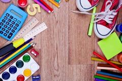 Schulbedarf auf einem hölzernen Hintergrund Stockbilder