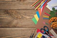 Schulbedarf auf einem Holztisch Lizenzfreie Stockfotografie