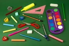 Schulbedarf auf grünem Hintergrund Stockbilder