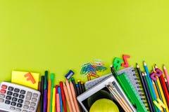 Schulbedarf auf grünem Hintergrund Lizenzfreies Stockbild