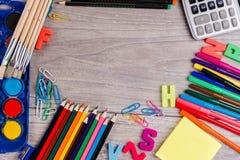 Schulbedarf auf hölzernem Hintergrund Stockbild