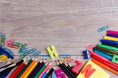Schulbedarf auf hölzernem Hintergrund Lizenzfreie Stockbilder