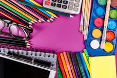 Schulbedarf auf purpurrotem Hintergrund Lizenzfreie Stockfotografie