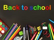 Schulbedarf auf schwarzem Hintergrund mit einfachem buntem Text lizenzfreies stockbild