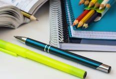 Schulbedarf, Briefpapier, mehrfarbige Bleistifte, Stift, Leuchtmarker, öffnete Mathearbeitsbuch auf dem weißen Desktop und lernte Lizenzfreies Stockbild
