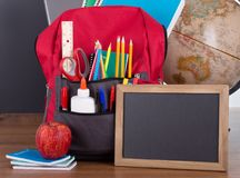 Schulbedarf in einem Bookbag und in einer leeren Tafel Lizenzfreie Stockfotografie