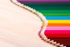 Schulbedarf färbte die Bleistifte, die eine Welle, auf einem hölzernen Hintergrund bilden Stockfoto
