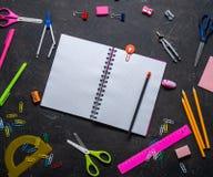 Schulbedarf für Schule: Notizblock, Bleistifte, rosa Machthaber, Kompassse zerstreute auf eine graue Tabelle Beschneidungspfad ei lizenzfreie stockfotografie