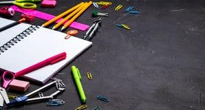 Schulbedarf für Schule: Notizblock, Bleistifte, rosa Machthaber, Kompassse zerstreute auf eine graue Tabelle Beschneidungspfad ei stockfoto