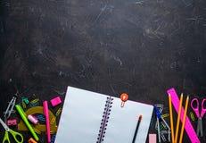 Schulbedarf für Schule: Notizblock, Bleistifte, rosa Machthaber, Kompassse zerstreute auf eine graue Tabelle Beschneidungspfad ei stockfotografie