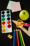 Schulbedarf - Farbe, Bleistifte, Scheren, ein Machthaber und großer grüner Apfel Lizenzfreie Stockfotos