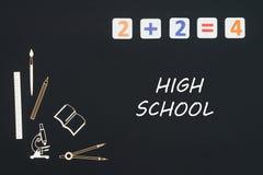 Schulbedarf gesetzt auf schwarzen Hintergrund mit Highschool des Textes lizenzfreies stockbild