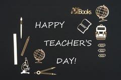 Schulbedarf gesetzt auf schwarzen Hintergrund mit ` s Lehrer des Textes glücklichem Tag lizenzfreie stockfotografie