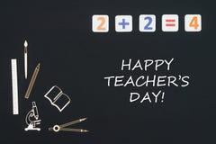 Schulbedarf gesetzt auf schwarzen Hintergrund mit ` s Lehrer des Textes glücklichem Tag stockbild
