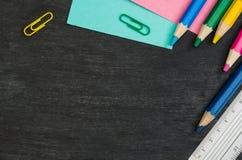 Schulbedarf grenzt an schwarzen Tafelhintergrund an Draufsichtphotographie stockfotografie