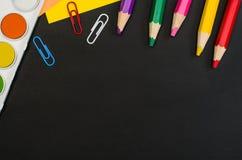 Schulbedarf grenzt an schwarzen Tafelhintergrund an Draufsichtphotographie lizenzfreie stockfotos