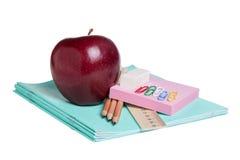 Schulbedarf mit Apfel Stockfotografie