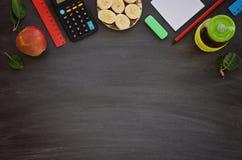 Schulbedarf, Sandwich und Saft in der Flasche auf kreideartigem Hintergrund Lizenzfreies Stockbild
