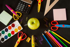 Schulbedarf und Apfel vor einer Tafel Stockbilder