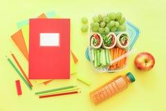 Schulbedarf und Brotdose mit geschmackvollen Rollen, Gurken, Karotten, Trauben, Apfel, Flasche Saft auf hellgelbem Lizenzfreies Stockfoto