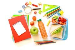 Schulbedarf und Brotdose mit Sandwichen, Stücken Gurken und Karotten, Aprikose, Kirschen, Apfel, Flasche von Stockbilder
