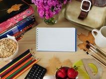 Schulbedarf und Frühstücksbestandteile auf einem Holztisch Stockbild