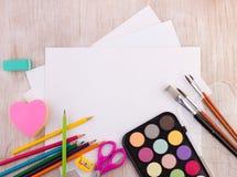 Schulbedarf und leeres Papier auf Schreibtisch lizenzfreie stockbilder
