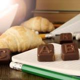 Schulbedarf und Schokolade berechnen der Buchstaben auf einem Notizbuch Lizenzfreie Stockfotografie
