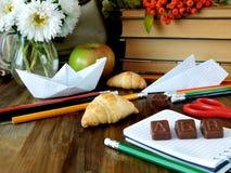 Schulbedarf und Schokolade berechnen der Buchstaben auf einem Notizbuch Stockfoto
