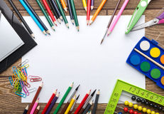 Schulbriefpapierrahmen auf hölzernem Hintergrund: Papier, Bleistift, Bürste, Scheren, Ordner, Abakus,
