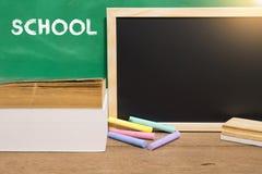 Schulbuch- und Schwarzbrett auf Schreibtisch getrennte alte Bücher Lizenzfreie Stockfotografie