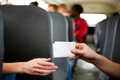 Schulbus: Mädchen, die Anmerkungen über Gang übergeben Stockbild