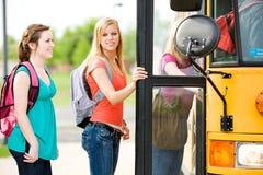 Schulbus: Mädchen schaut, um beim Verschalen des Busses mit Seiten zu versehen Stockfotos