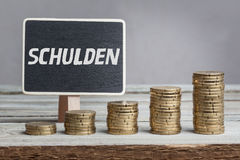 Schulden (debts) in German language. White chalk type on black board, Euro money coin stacks of growth on wood table Royalty Free Stock Photography