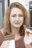 Schuldige Frau auf Diät Schokoriegel zu Hause essend Stockfotos
