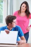 Schuldige Tiener die Internet verbergen die van Moeder doorbladeren Stock Foto