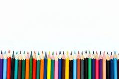 Schule-children& x27; s färbte Bleistifte ausgebreitet in der Linie auf einem weißen Hintergrund lizenzfreie stockfotografie
