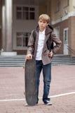 Schule jugendlich mit Schultasche und Skateboard Stockfotografie