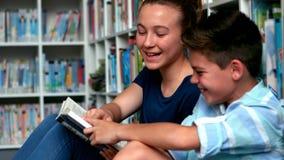 Schule scherzt Lesebücher in der Bibliothek in der Schule stock footage