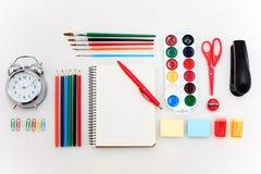 Schule stellte mit Notizbüchern, Bleistiften, Bürste, Scheren und Apfel auf weißem Hintergrund ein Stockbild