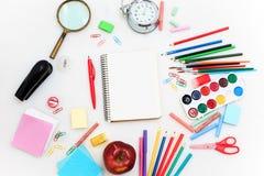 Schule stellte mit Notizbüchern, Bleistiften, Bürste, Scheren und Apfel auf weißem Hintergrund ein Lizenzfreies Stockbild