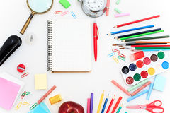 Schule stellte mit Notizbüchern, Bleistiften, Bürste, Scheren und Apfel auf weißem Hintergrund ein Stockfotografie